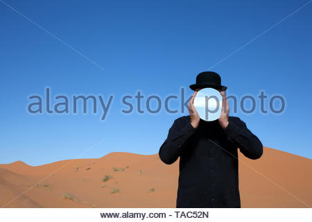 Morocco, Merzouga, Erg Chebbi, man wearing a bowler hat holding mirror in front of his face in desert dune - Stock Image
