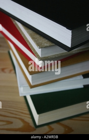 A variety of books stacked up on each other. - Stock Image