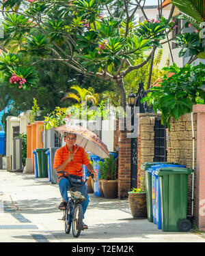 A man riding his bicycle while holding an umbrella. - Stock Image