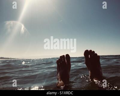 Feet floating in the ocean. Manhattan Beach, California USA. - Stock Image