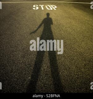 Gloomy shadow of  an anonymous person in front of STOP painted sign - Stock Image