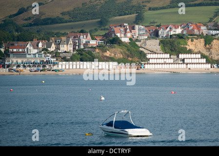 General view across Swanage Bay looking back at the beach, beach huts and cliff top houses. - Stock Image