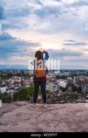 Girl is making selfie during warm summer sunset from Nebet tepe Hill in Plovdiv city, Bulgaria. - Stock Image