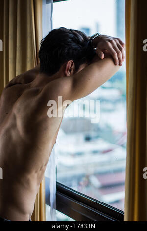 Sexy young man standing shirtless by curtains - Stock Image