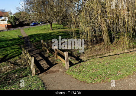 Bridge with wooden railings over the stream through Northolt village, will weeping willows in winter - Stock Image