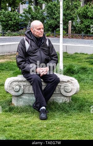 Elderly man sitting on Pedestal of the former Flora monument In Steinplatz square, Charlottenburg Berlin - Stock Image