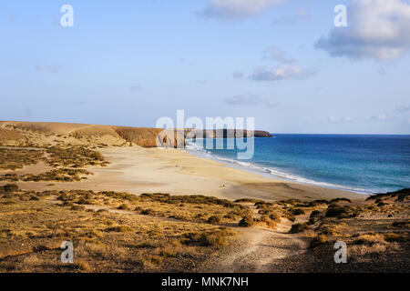 The evening sun casts a warm glow across Playa de las Mujeres beach in Lanzarote. the largest of the Papagayo beaches set in a nature reserve - Stock Image