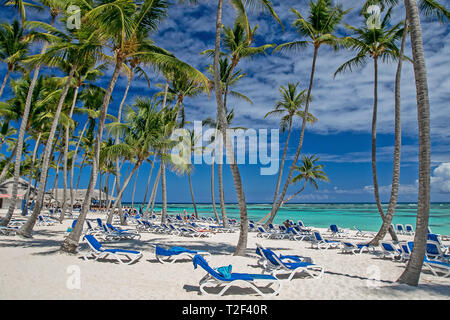 Tanning chairs with towels on a tropical resort's beach. - Stock Image