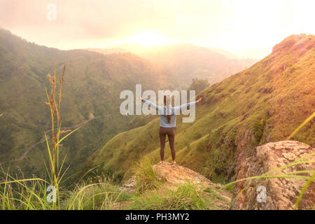 Sporty woman standing with raised arms on the top oh hill looking at sunrise. - Stock Image