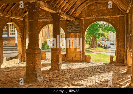 The old market hall in the centre of the Cotswold town of Chipping Campden with sunlight shining through the open - Stock Image