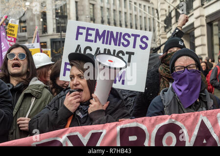London, UK. 9th Dec, 2018. Feminists against Fscism march behind a banner 'The Enemy doesn't arrive by boat - He arrives by Limousine. No to Fortress Britain', The united counter demonstration by anti-fascists marches in opposition to Tommy Robinson's fascist pro-Brexit march. The march which included both remain and leave supporting anti-fascists gathered at the BBC to to to a rally at Downing St. Police had issued conditions on both events designed to keep the two groups well apart. Credit: Peter Marshall/Alamy Live News - Stock Image
