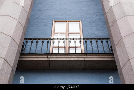 Window with Juliet wrought iron balcony between stone pillars and blue painted brickwork - Stock Image