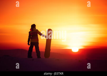 Woman snowboarder silhouette on sunset backdrop - Stock Image