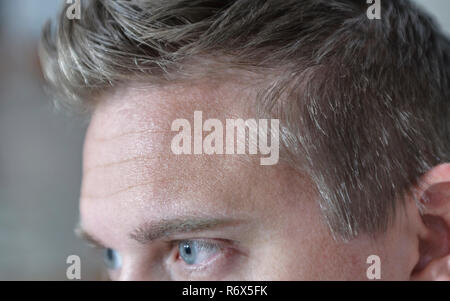 Close up sideview of adult man face and head with focus on his blue eyes looking ahead and concentrated - Stock Image