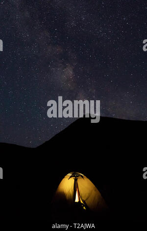 Illuminated tent by mountain at night - Stock Image