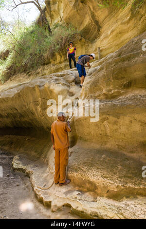 Tourists with guide climbing a short rope, Ol Njorowa gorge, Hells Gate National Park, Kenya - Stock Image