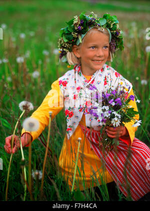 Girl in traditional Midsummer dress picking wild flowers for head crowns and Maypole in Sweden - Stock Image