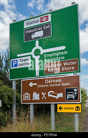 Large new green roundabout road primary route direction sign and brown tourist information sign, Oakham, Rutland, England, UK - Stock Image