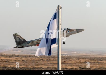 Hazerim Air Base, Israel. 27th June, 2019. IAF F-15i's demonstrate an aerial dog fight occasionally releasing flares to divert incoming heat seeking missiles at an air show at a graduation ceremony honoring newly certified Israel Air Force pilots and navigators following their successful completion of one of the most competitive and rigorous training processes in the IDF at Hazerim Air Base in the Negev Desert. Credit: Nir Alon/Alamy Live News. - Stock Image