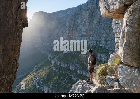 """Hiker looking out from the """"India Venster"""" rock formation on Table Mountain in Cape Town. - Stock Image"""