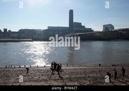 View of River Thames at low tide Tate Modern Art Gallery building & children people mudlarking near Millennium Bridge in London UK  KATHY DEWITT - Stock Image