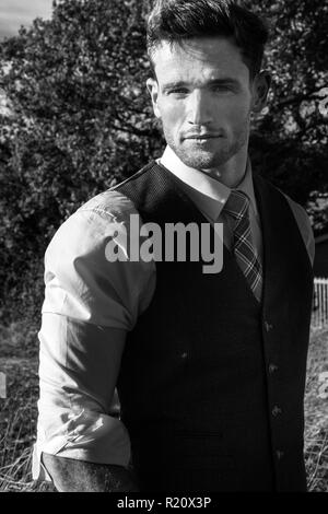 Handsome man wearing a suit in countryside with trees and fields in background - Stock Image
