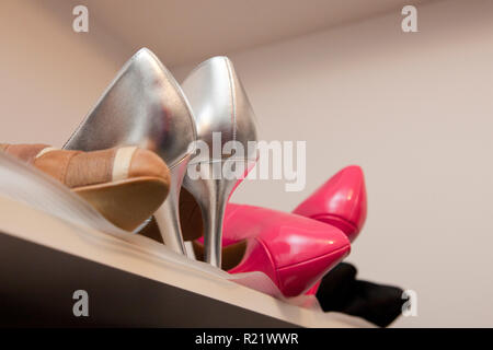 Collection of heels and shoes on top shelf of closet - Stock Image