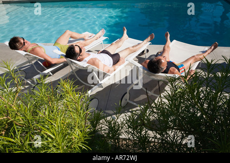 Men relaxing in lawn chairs beside swimming pool - Stock Image