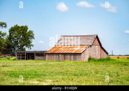 An old American wooden barn on farmland in Kansas, USA. - Stock Image