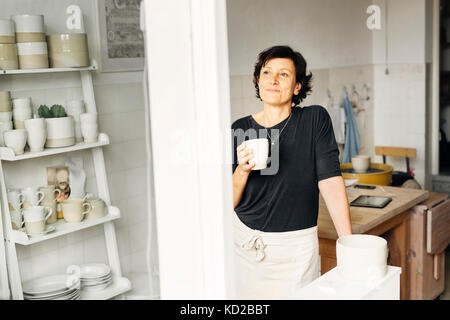 Potter holding coffee cup - Stock Image