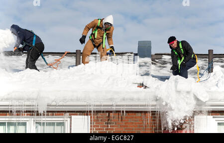 Lexington, MA, USA, 21 Feb, 2015. Workmen cleaning snow from the roof of a three story apartment building in Lexington, - Stock Image