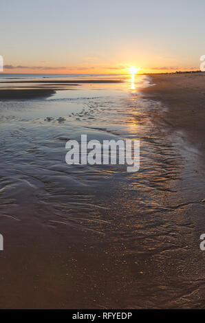Low tide forming floods, wetlands, at beach, Atlantic Ocean, dring sunset, sunrise, Algarve, Portugal, Europe - Stock Image
