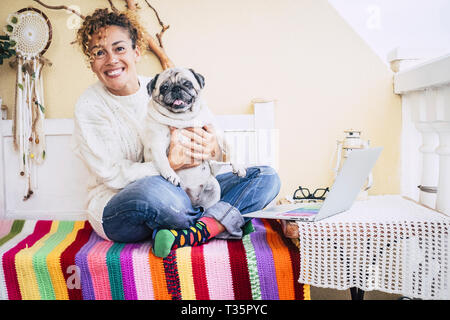 Happy couple at home with pretty middle age woman and funny dog pug - love and affection people with animals - hug and cheers at the camera portrait - - Stock Image