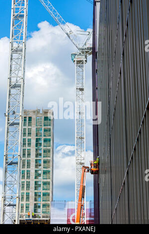A worker on an aerial platform and tower cranes, at the Circle Square office and residential development, Oxford Road, Manchester, England, UK - Stock Image