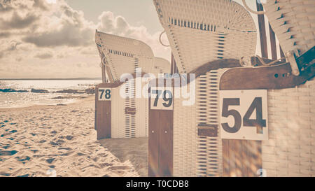 Retro stylized picture of wicker beach chairs on a beach against the sun with lens flare, selective focus. - Stock Image