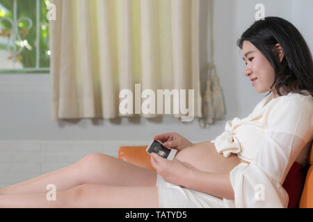Asian beautiful pregnant woman see ultrasound photo on sofa in home background. - Stock Image