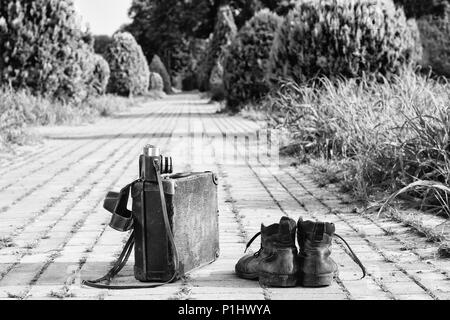 Traveling light! Worn ankle boots next to a vintage cardboard suitcase, a film camera in its open leather case, and a brick road. A B/W photo effect. - Stock Image