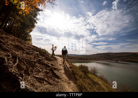 Male backpackers walking on dirt road against cloudy sky - Stock Image