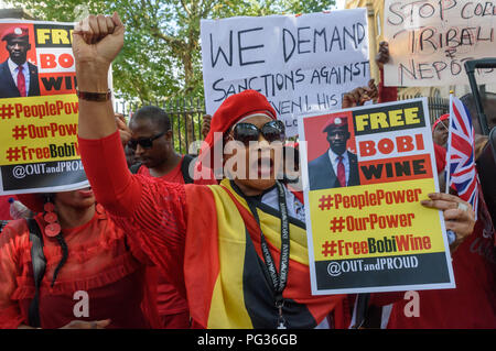 London, UK. 23rd August 2018. Hundreds of Ugandans, mainly dressed in red, protest at Downing St to say that President Museveni must go. They accuse him of being a dictator, and called for and end to the killing of opposition politicians and for  the release of those imprisoned, including business man, MP and singer Bobby Wine (Robert Kyagulanyi Ssentamu), and an end to land grabbing. Credit: Peter Marshall/Alamy Live News - Stock Image