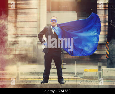 A businessman superhero with a blue cape standing in the city for a determination, confidence or success concept. - Stock Image