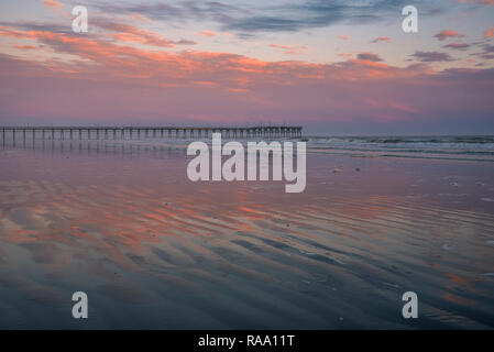 Sunset with pink clouds and fishing pier, Sunset Beach, North Carolina, United States - Stock Image