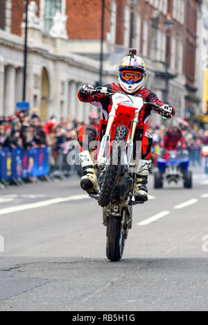 Moto Stunts International motorbike display team at London New Year's Day Parade. Motorcycle wheelie in Whitehall - Stock Image