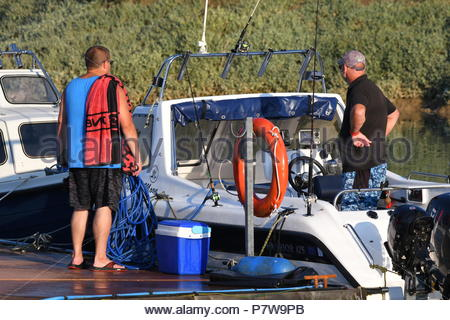 Littlehampton, UK. Sunday 8th July 2018. Men chatting on a boat on a very warm evening at Littlehampton Marina, near the South Coast. Credit: Geoff Smith / Alamy Live News. - Stock Image