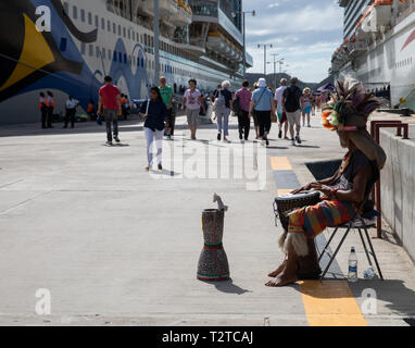 A man plays a drum as people arrive on a cruise ship in Saint John's, Capital of Antigua and Barbuda - Stock Image