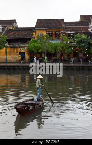 A woman in traditional conical hat rows a boat in the main canal in the UNESCO World Heritage Site town of Hoi An, in Central Vietnam. - Stock Image