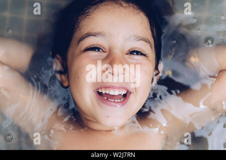 portrait of a happy pretty little girl laughing lying in the tub while taking a bath in the bathtub, kids hygiene concept - Stock Image