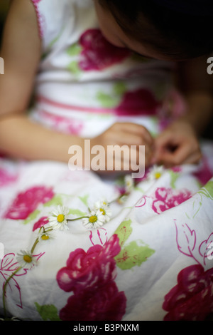 Five year old girl makes daisy chain - Stock Image