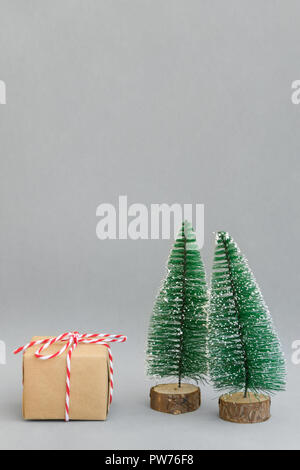 One gift box wrapped in craft paper tied with red white ribbon Christmas trees on grey background. New Year corporate presents shopping concept. Poste - Stock Image