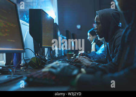 Serious smart coders sitting in line in dark server room and using modern computers while working on apps - Stock Image