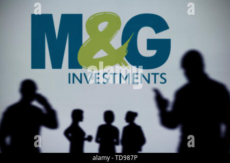 The M&G Investments logo is seen on an LED screen in the background while a silhouetted person uses a smartphone in the foreground (Editorial use only - Stock Image